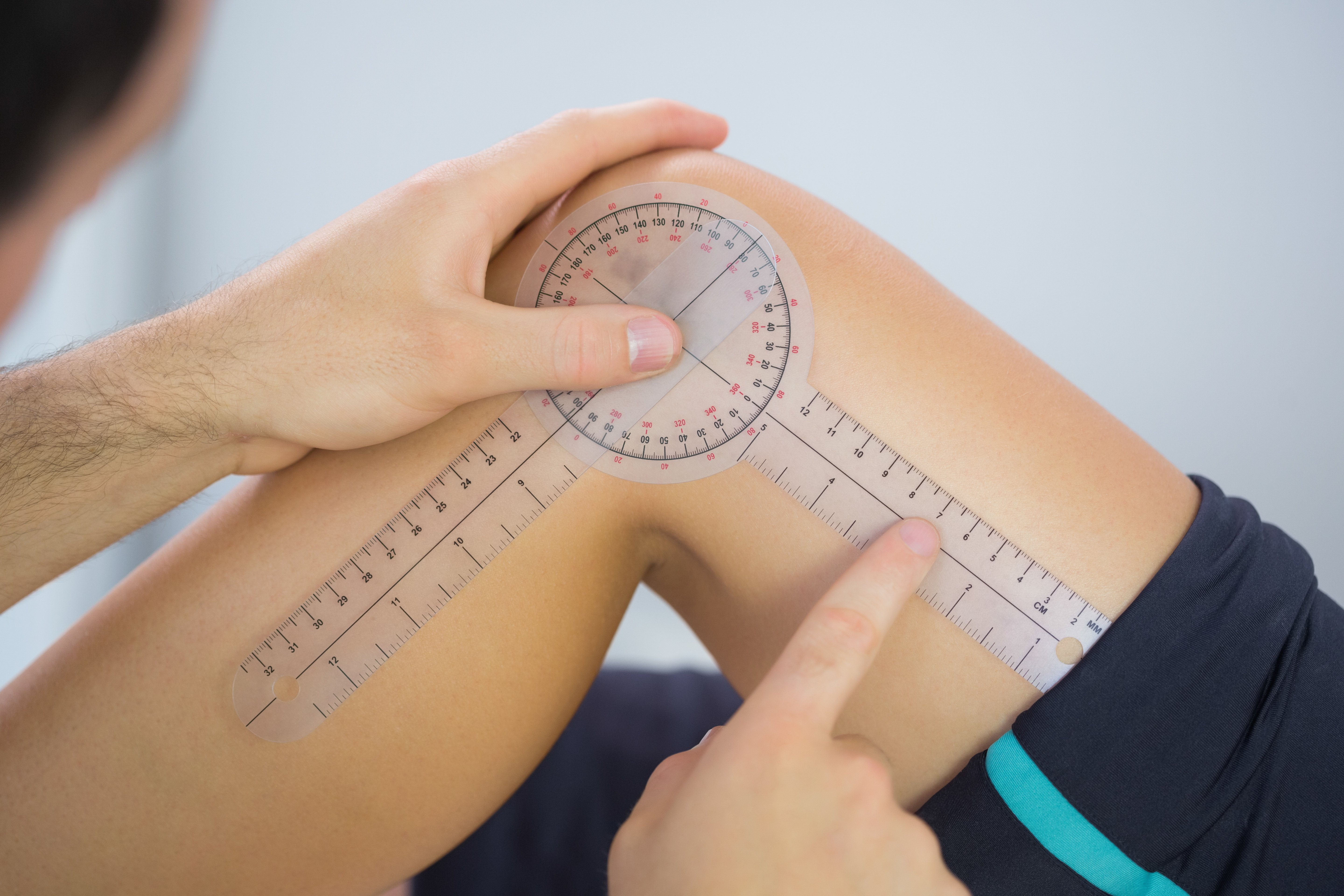 Physiotherapist examining knee angle with goniometer in bright office